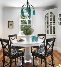 dining room set up country style round dining table dark chairs white cushions