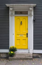 contemporary yellow house dark red door shutters throughout design
