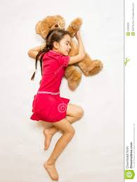 in pink dress sleeping on big teddy bear on floor stock photo