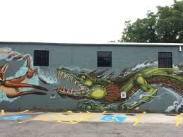 a guide to 21 works of street art you must see right now on an exterior wall of the argosy the wasp at 435 oakview in decatur and a gorgeous purple lizard dragon piece on the railroad wall in cabbagetown