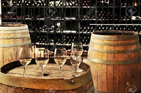row of wine glasses on barrel in winery cellar stock photo