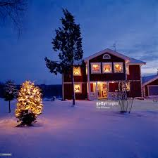 christmas tree lit up at dusk in front of a house vastergotland