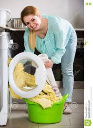 portrait of housewife with bed linen near washer stock photo