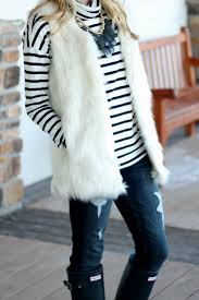 white faux fur vest with a striped sweater and hunter boots the