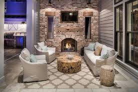 Moroccan Outdoor Rug Covered Patio With Red Brick Fireplace Fitted With Flat Panel Tv