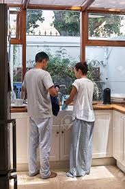 young happy couple doing household chores washing and drying