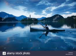slovenia lake man canoeing on lake bled slovenia with the island church of the