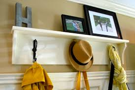 white wooden wall coat rack shelf with three hangers on the wall