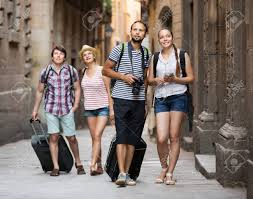 Company of smiling young travelers with travel bags walking the