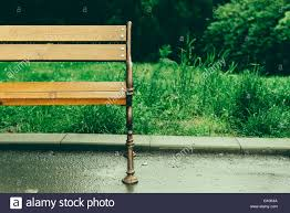 half of an empty bench outside in the park after a rain with stock