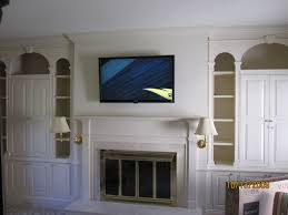 tv above fireplace concealing wires in the wall over the