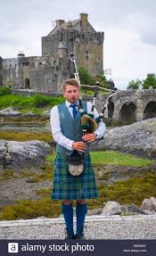 young man in traditional scottish kilt with bagpipe in front of