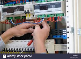 electrician wiring up a switchboard in a new building stock photo