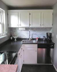 lovely small kitchen with black laminate countertops and marble