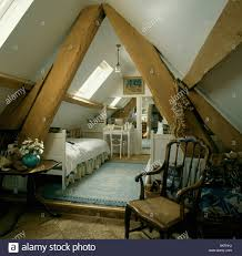 Attic Bedroom by Large Wooden Support Beams In Attic Bedroom With Apex Roof Stock