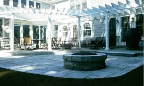 backyard custom natural stone patio with a gas fire pit