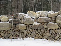 this drystonewall looks upside down with large boulders on top