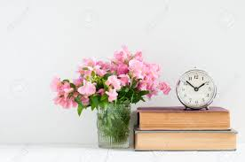 retro home decor a stack of books flowers and a vintage alarm