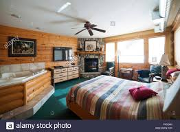 hotel suite with tub and fireplace in log lined bedroom two