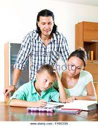 parents and teenager helping with homework in home interior   Stock Image Alamy