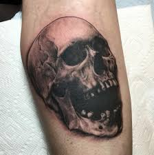 realistic black and grey skull tattoo by nic lebrun tattoos