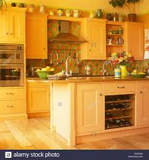 green orange tiles and island unit with integral wine storage in