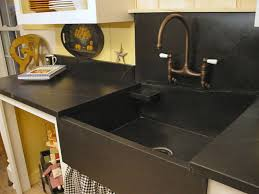 traditional kitchen designed with black countertops and stone sink