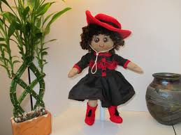 cowgirl dressed in black dress trimmed with red and a red hat and