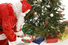 santa claus putting gifts the tree white background