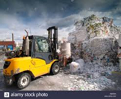 forklift truck with clamp grip at paper recycling factory plant in