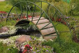 garden arched bridge little artificial pond and flowers in the