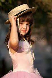 Cute girl is fitting a straw hat  Stock Photo  Colourbox
