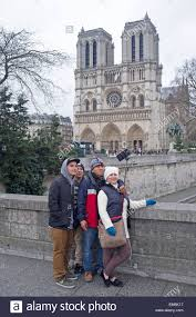 a family take a selfie in front of the notre dame cathedral stock