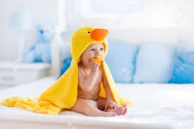happy laughing baby wearing yellow hooded duck towel sitting