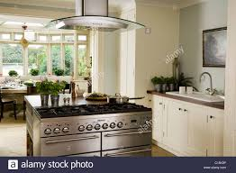 modern white kitchen with stainless steel island hob and extractor