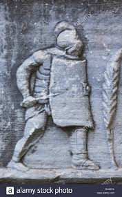 bas relief of a roman soldier with helmet sword and shield