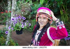 a flower hmong women wearing traditional costume steps through the