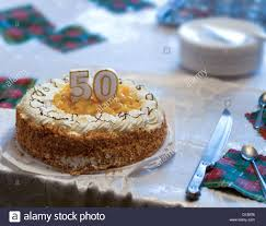 50th birthday cake on table in poor family stock photo royalty