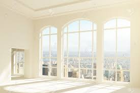 sunny white loft interior with big windows and city view stock