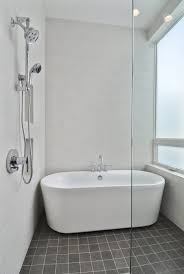 small corner white bathtub and brown ceramic tiled wall panel with minimalist
