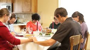 extended family praying together before dinner at home in the