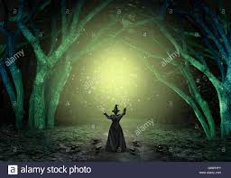 green halloween background magical witch casting a magic spell in a scary dark mystery forest