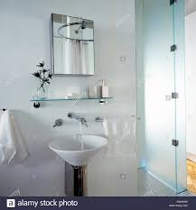 Glass Bathroom Shelving Unit by Mirrored Cabinet And Glass Shelf Above Circular Basin On Chrome