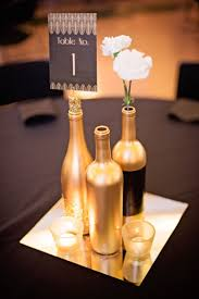 wine bottle plates gold and glitter wine bottles as the table centerpieces for