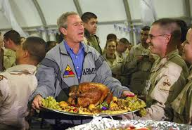 us president bush holds turkey during visit to troops in