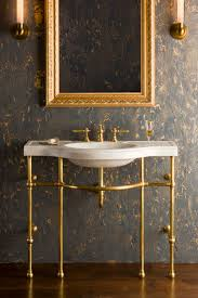 4 leg curved console shown in brass with carrara marble sink