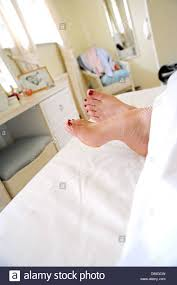 female feet with red painted toe nails sticking out of the end of
