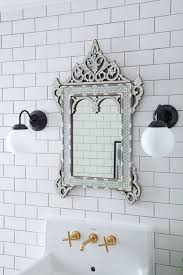 Brass Bathroom Fixtures by Bathroom With Subway Tiles And Ornate Mirror Over Sink With Brass