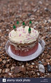 a birthday cake with champagne candles on a pebbled beach stock