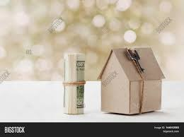 model of cardboard house with key and dollar bills house building